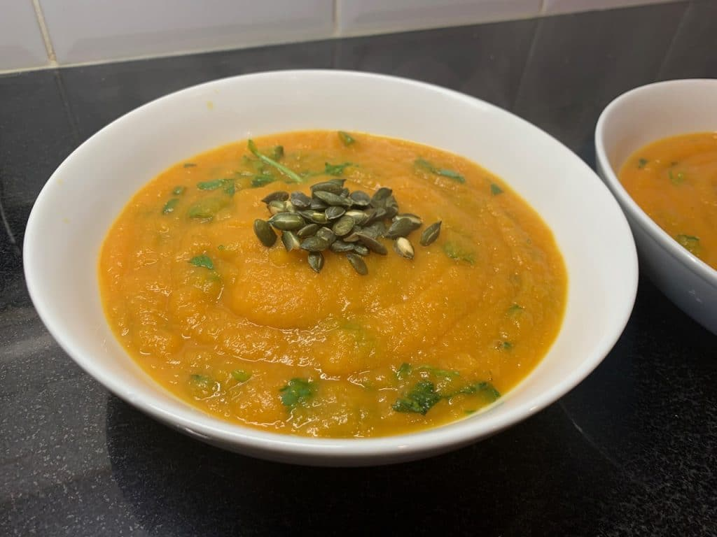 Spicy carrot and coriander soup with toasted pumpkin seeds